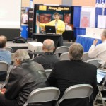 A speaker from IMAGINiT Technologies makes a presentation at the stage in the Exhibit Hall