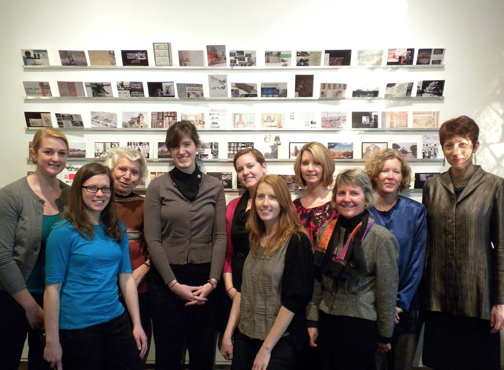Donna Dunay with students standing in front of an exhibition created to highlight the IAWA