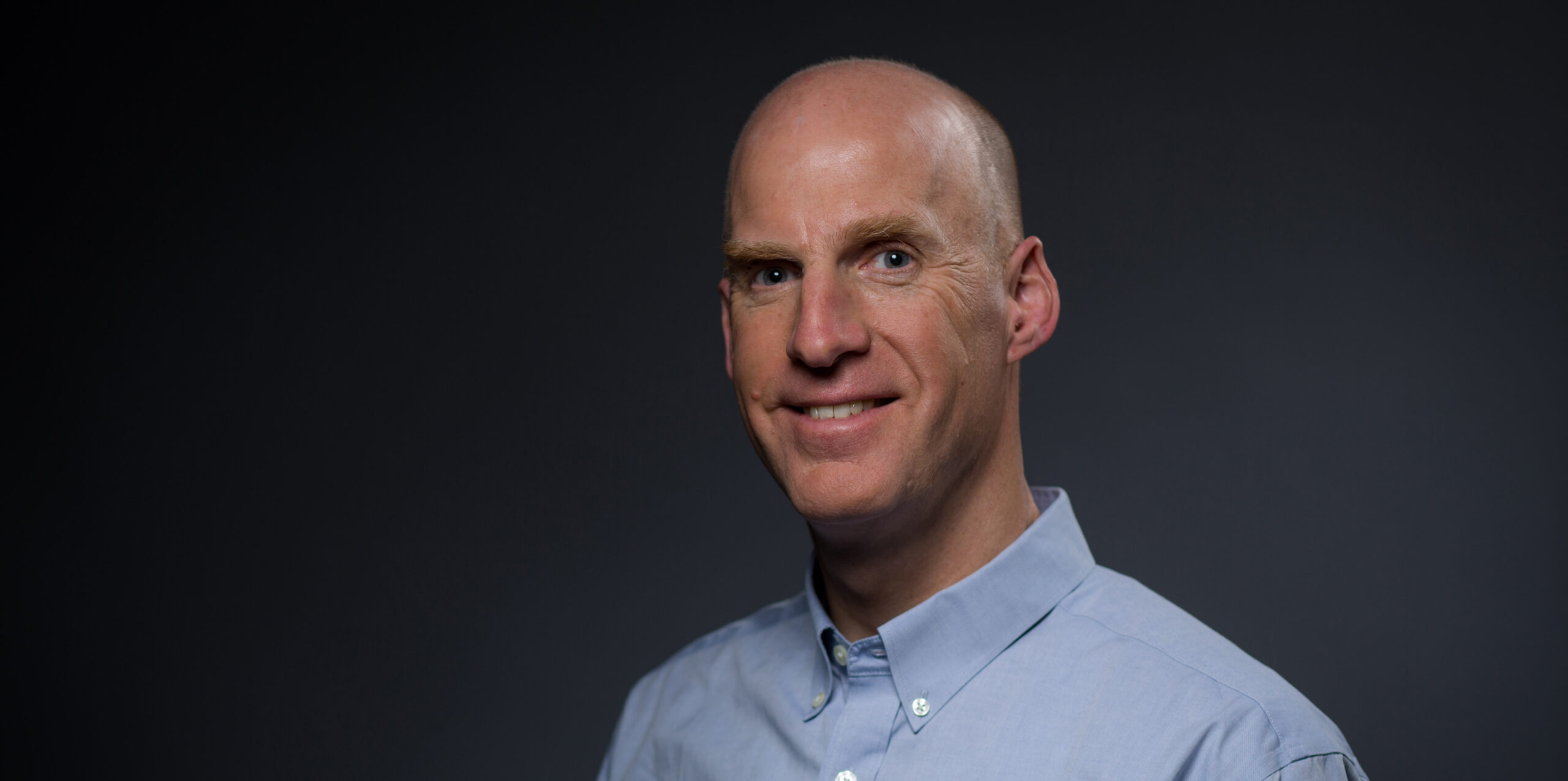 Architect Chris Downey in a blue shirt with a dark background.